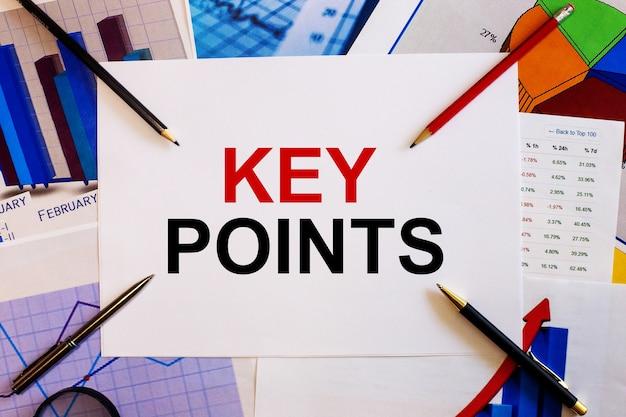 Key pointsという言葉は、色付きのグラフ、ペン、鉛筆の近くの白いテーブルに書かれています。ビジネスコンセプト