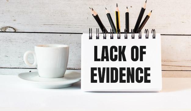 В белом блокноте рядом с белой чашкой кофе на светлом фоне написано недостаток доказательств.