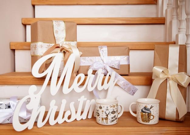 メリークリスマスという言葉と木製の階段のクラフト紙の贈り物環境にやさしいコンセプト
