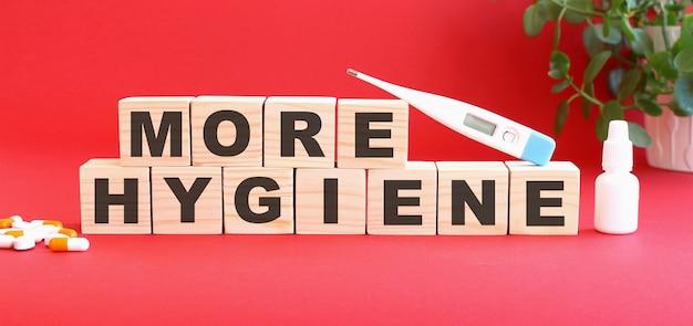 More hygiene이라는 단어는 의료용 약물과 함께 빨간색 배경에 나무 큐브로 만들어집니다.