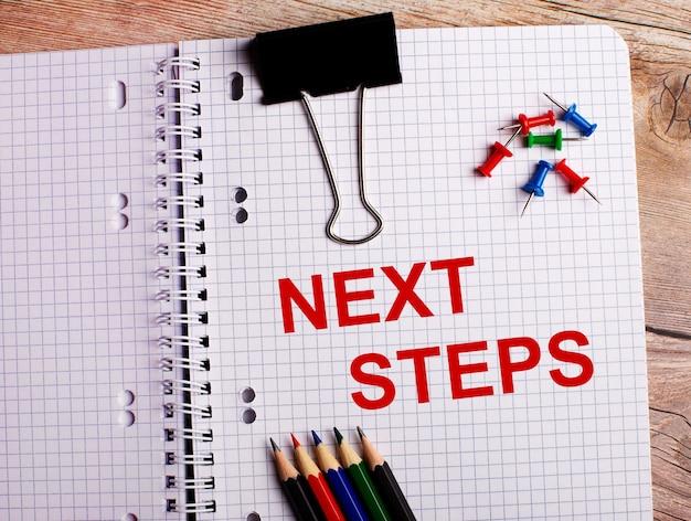 Next stepsという言葉は、木製の背景にあるマルチカラーの鉛筆とボタンの近くのノートに書かれています