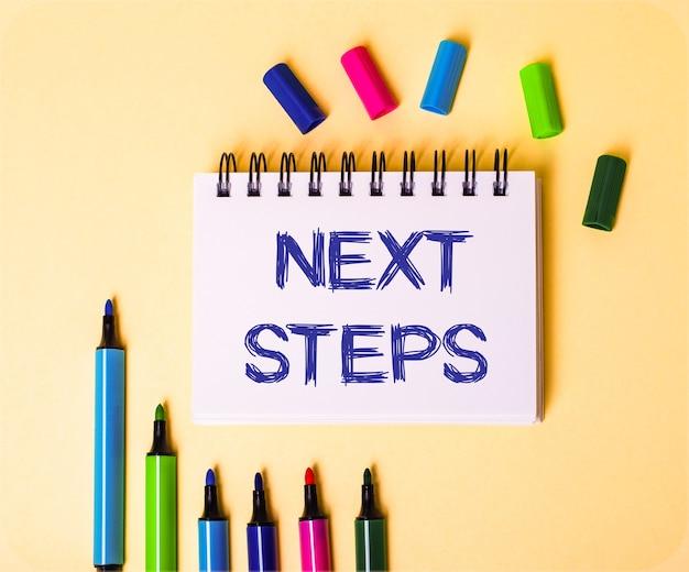 マルチカラーマーカーの近くのベージュの背景に白いノートに書かれた「次のステップ」という言葉