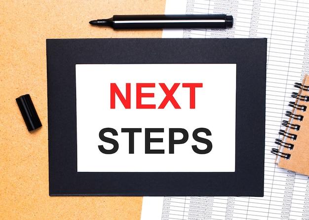 コーヒーカップと日記の近くの茶色の表面に黄色い紙に書かれた「次のステップ」という言葉