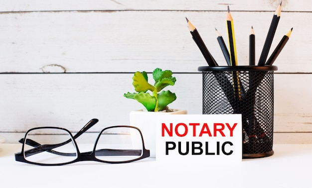 Слова «нотариус» написаны на белой визитной карточке рядом с карандашами в стойке и очками. рядом растение в горшке.
