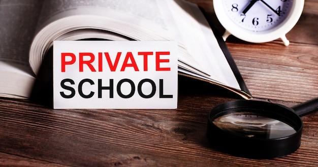 開いた本、目覚まし時計、虫眼鏡の近くの白いカードに書かれた私立学校という言葉