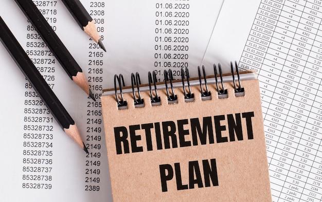茶色のノートには「退職年金」という言葉が書かれています。近くの鉛筆