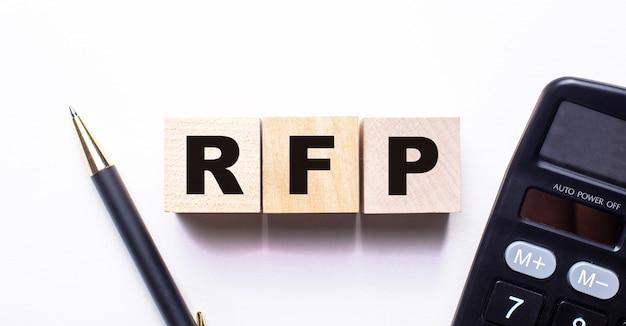 제안에 대한 rfp 요청이라는 단어는 밝은 배경에 펜과 계산기 사이의 나무 큐브에 기록됩니다.