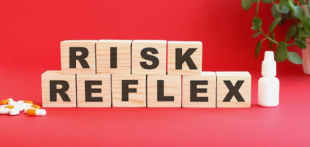 Risk reflex라는 단어는 의료용 약물로 붉은 색 표면에 나무 큐브로 만들어져 있습니다.