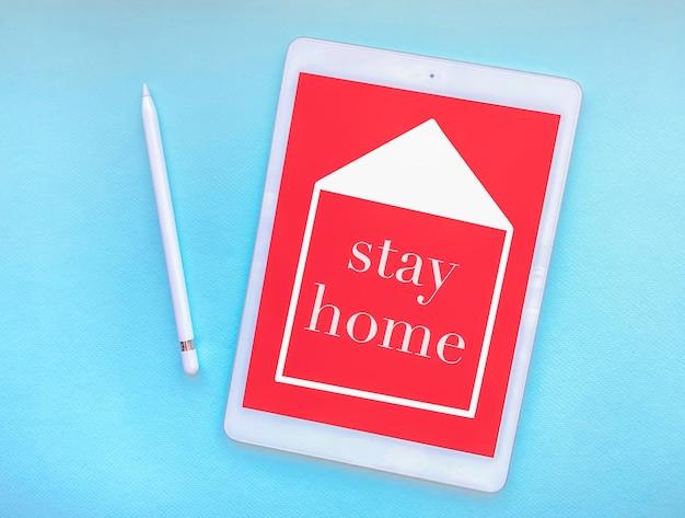 コロノウイルス病の蔓延を防ぐための予防策としての自宅での検疫の概念であるタブレット画面では、この言葉は家に留まります。