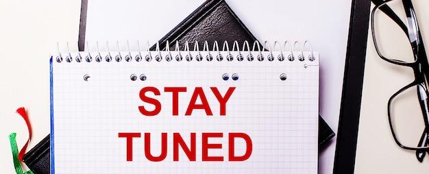 Надпись stay tuned написана красным в белом блокноте рядом с очками в черной оправе.