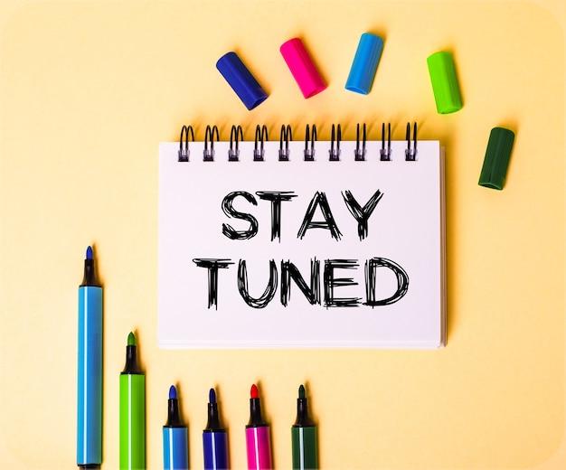 Надпись stay tuned написана в белой записной книжке на бежевой стене возле разноцветных маркеров.