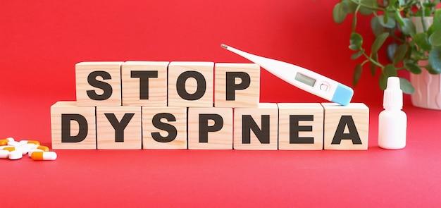 Stop dyspnea라는 단어는 의료용 약물과 함께 빨간색 배경에 나무 큐브로 이루어져 있습니다.