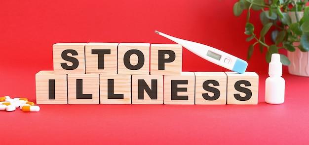 Stop illness라는 단어는 의료용 약물과 함께 빨간색 배경에 나무 큐브로 구성됩니다.