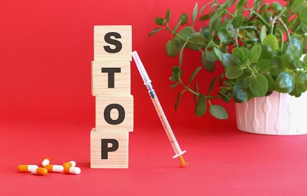 Stopという言葉は、赤い背景に木製の立方体でできています。医療の概念。