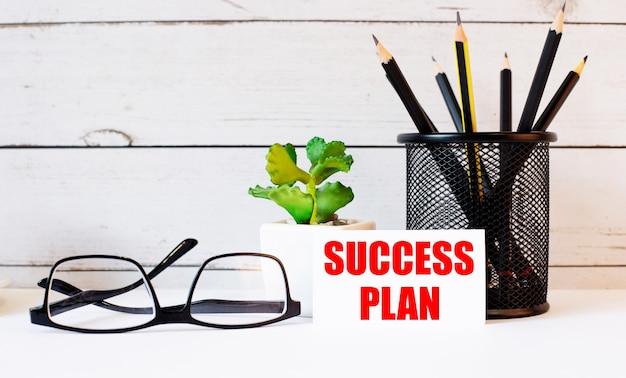 スタンドとメガネの鉛筆の横にある白い名刺に書かれたsuccessplanという言葉。近くには鉢植えがあります。