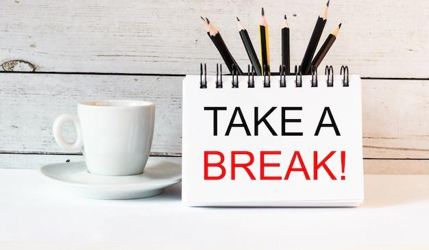 Слова «сделай перерыв» написаны в белом блокноте возле белой чашки кофе на светлом фоне.