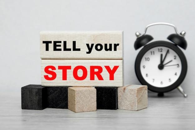 자명종 시계와 함께 나무 큐브에 쓰여진 tell your story라는 단어.
