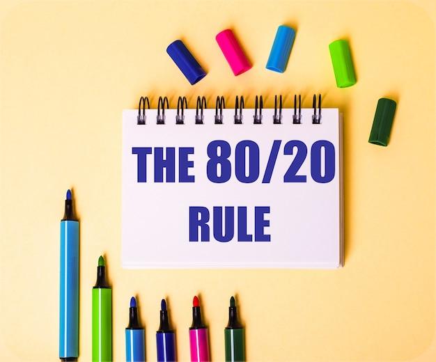 여러 가지 색의 마커 근처의 베이지 색 표면에 흰색 노트북에 쓰여진 80 20 규칙이라는 단어.