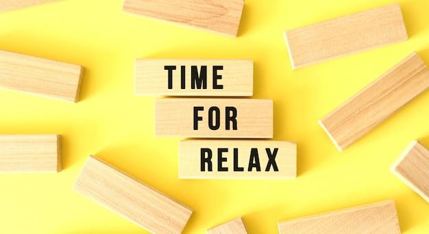 Time for relax라는 단어는 노란색 배경에 흩어져 있는 나무 블록에 쓰여 있습니다. 비즈니스 개념