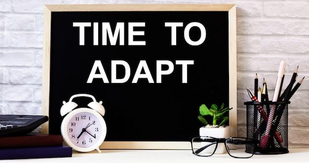 Слова «время адаптировать» написаны на доске рядом с белым будильником, очками, горшечным растением и карандашами на подставке.