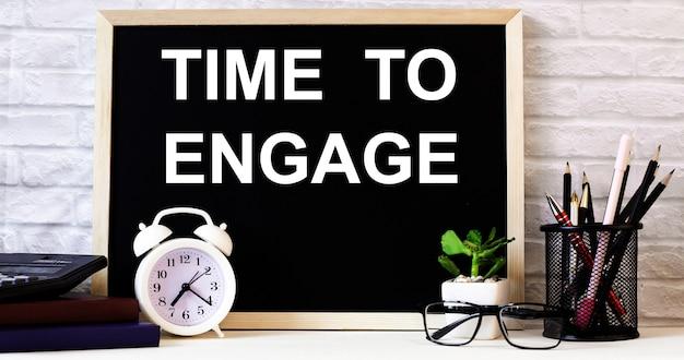 На доске рядом с белым будильником, очками, горшечным растением и карандашами на подставке написаны слова «время задержать».