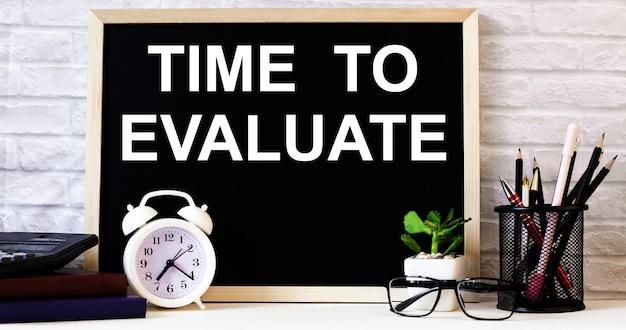 Слова «время оценить» написаны на доске рядом с белым будильником, очками, горшечным растением и карандашами на подставке.