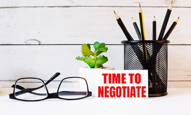 スタンドとメガネの鉛筆の横にある白い名刺に書かれた「交渉する時間」という言葉