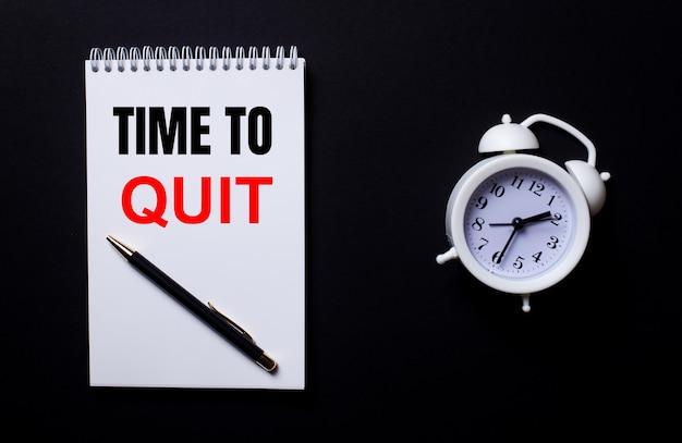 Time to quitという言葉は、黒い背景の白い目覚まし時計の近くにある白いメモ帳に書かれています。