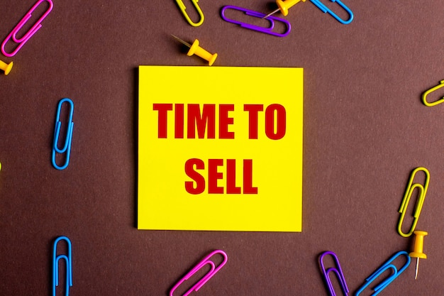 Слово «время продать» написано красным на желтой наклейке на коричневом фоне рядом с разноцветными скрепками.