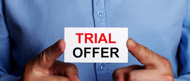 Trial offerという言葉は、男の手の白い名刺に書かれています。ビジネスコンセプト