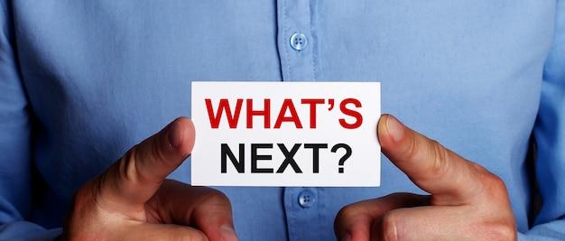 「次は何か」という言葉は、男の手の白い名刺に書かれています。ビジネスコンセプト