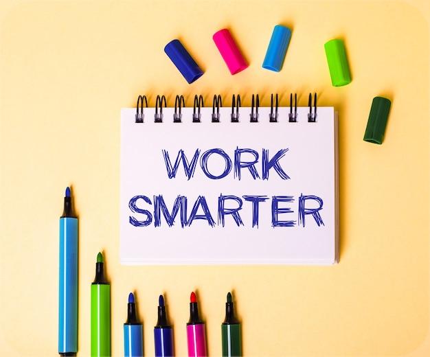 멀티 컬러 마커 근처의 베이지 색 배경에 흰색 노트북에 쓰여진 work smarter라는 단어