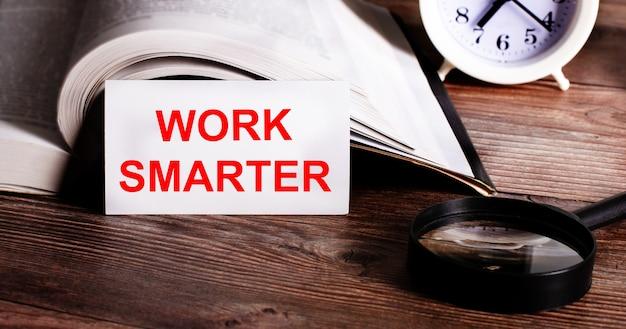 Слова работайте умнее, написанные на белой карточке рядом с открытой книгой, будильником и увеличительным стеклом