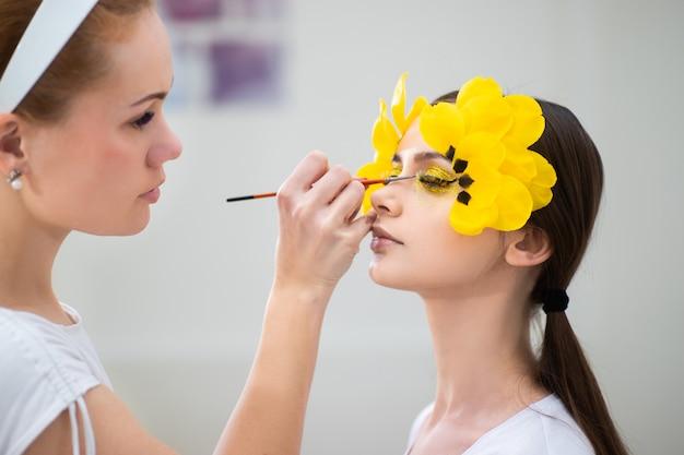 Работа визажиста. портрет красоты брюнет с длинными ресницами в форме тюльпана. глаз крупным планом