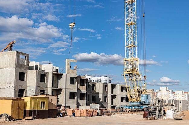 일몰 하늘을 배경으로 타워 크레인의 작업. 현대 주택 건설입니다. 산업 공학. 모기지 주택 건설.