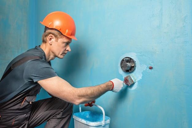 Рабочий наносит гидроизоляционную краску на стену в ванной комнате