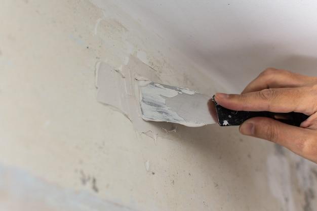 労働者はでこぼこの壁、へらとパテで男の手を覆い、アパートの修理