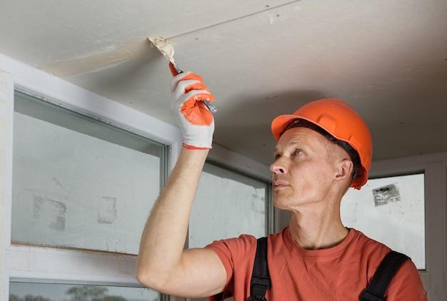 Рабочий заполняет швы гипсокартона гипсовой шпаклевкой.