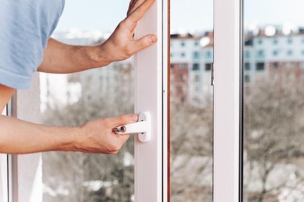 Рабочий устанавливает и проверяет окно в доме