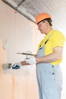 Рабочий наносит шпаклевку на сетку из стекловолокна на стене