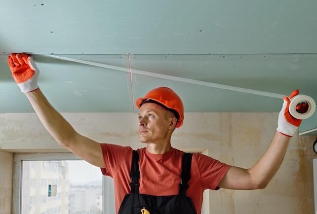 Рабочий прикрепляет сетку к швам между гипсокартонами.