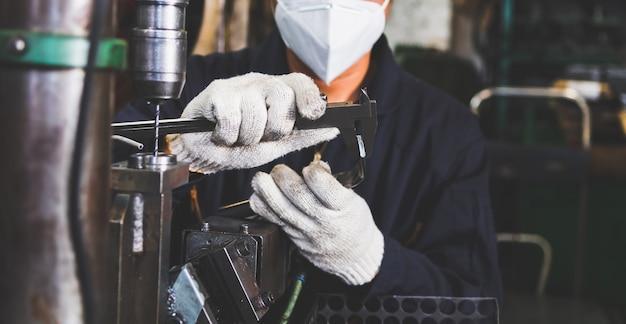 作業員は、工場の金属細工のノギスで金属部品の品質サイズとデザインをチェックしています。金属部品の製造と品質のチェック。
