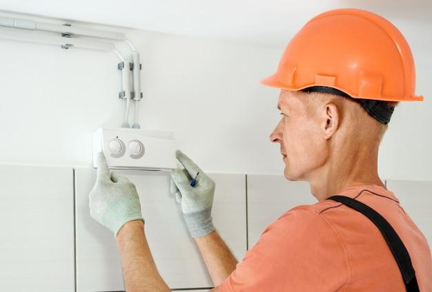作業員は換気システムの湿度センサーを接続しています。