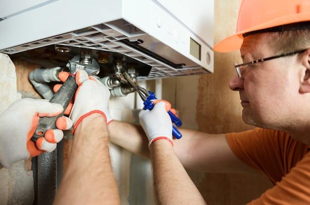 작업자가 파이프를 가정용 가스 보일러에 연결하고 있습니다.
