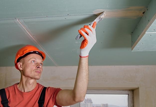 Рабочий заполняет швы гипсокартона гипсовой шпатлевкой.