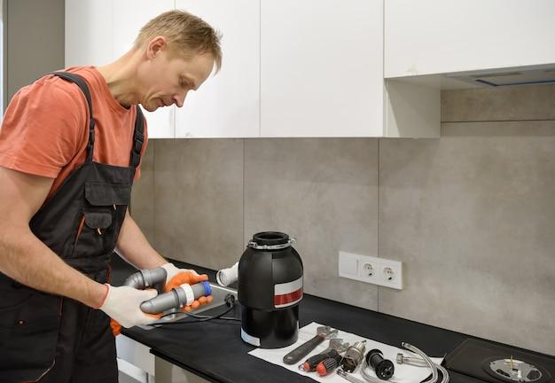 작업자가 주방 싱크대에 가정용 쓰레기 분쇄기를 설치하고 있습니다.