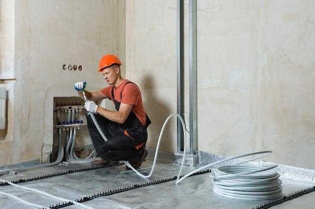 작업자가 아파트의 따뜻한 바닥에 파이프를 설치하고 있습니다. 그는 확장 파이프입니다.