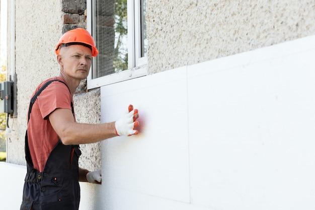 労働者はファサードに発泡スチロールの板を設置しています