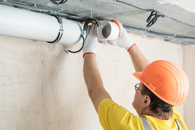 Рабочий устанавливает в квартире систему вентиляции.