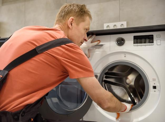 작업자가 주방 가구에 세탁기를 설치하고 있습니다.